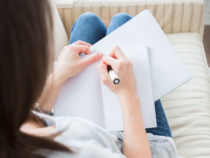woman writing on paper writing a book