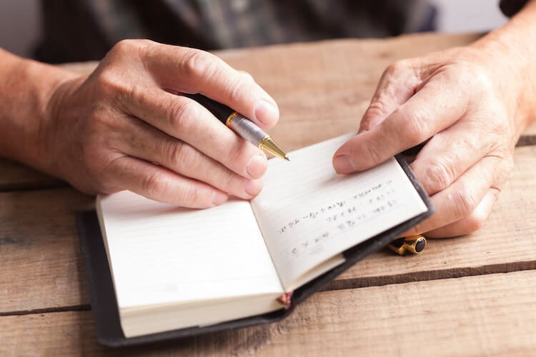 man writing in journal Daily journal prompts